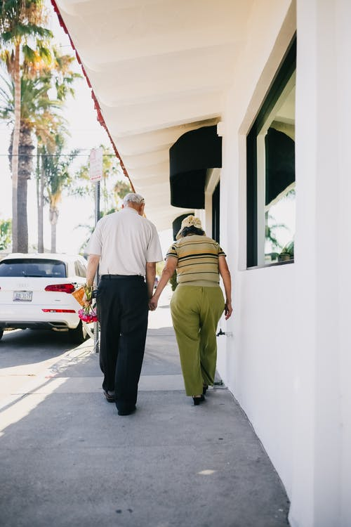 Elderly Couple Walking With Holding Hands On Sidewalk