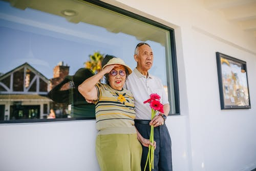 Elderly Couple Standing Beside A Glass Window