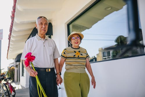 Elderly Couple Holding Hands and Holding Red Flowers while Walking