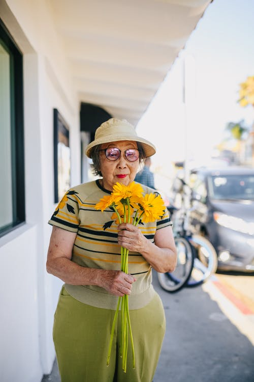Elderly Woman Holding Yellow Flowers