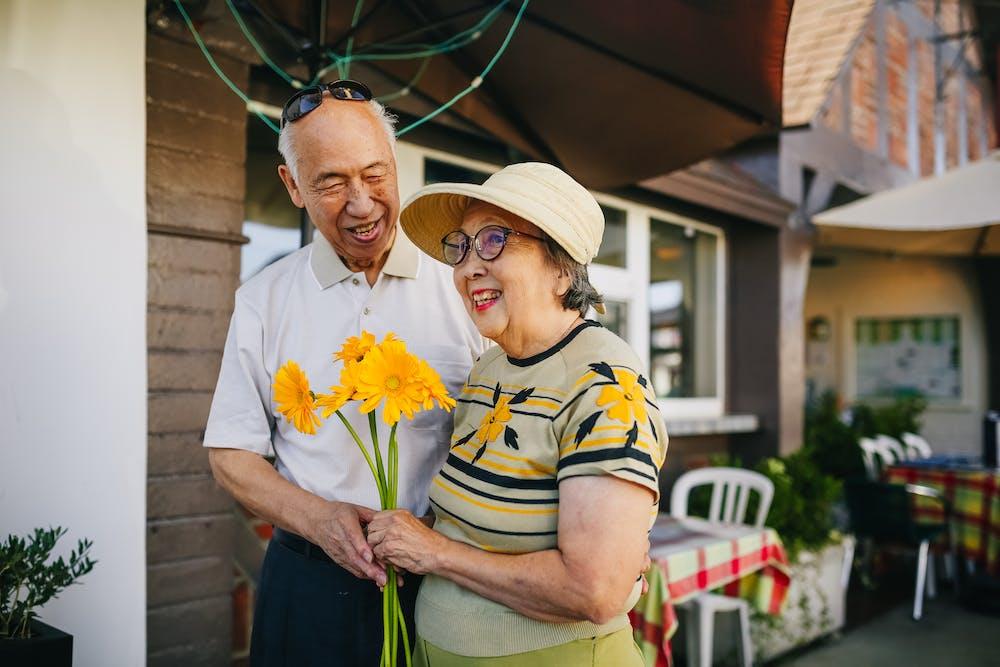 Elderly couple holding bouquet of flowers.   Photo: Pexels