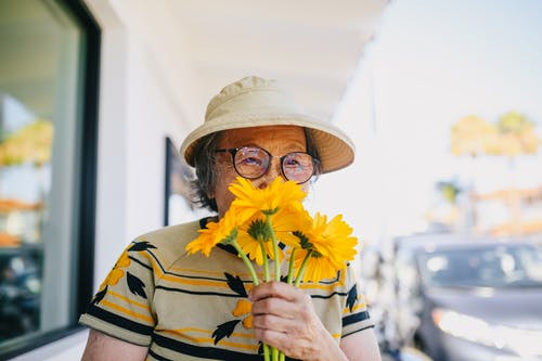 Elderly Woman Smelling Yellow Flowers