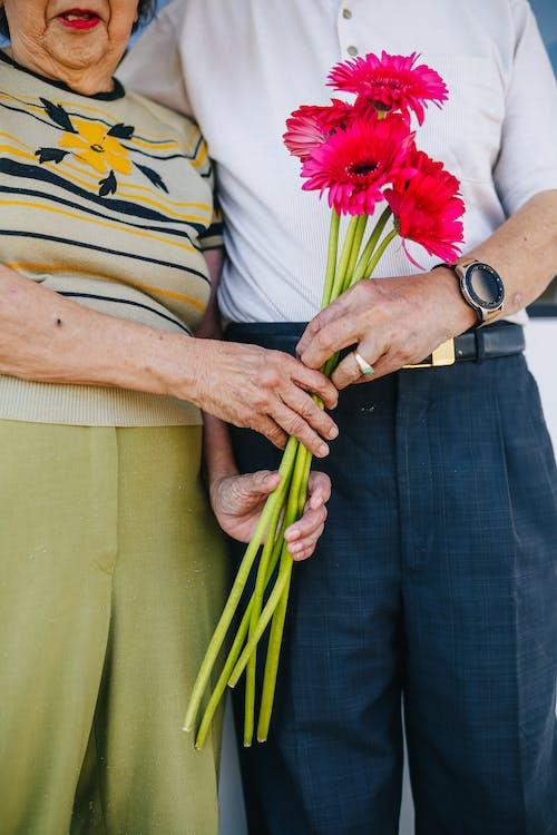 Elderly Couple Holding Red Flowers