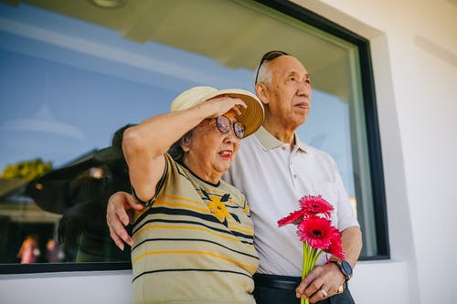 Elderly Couple Holding Red Flowers