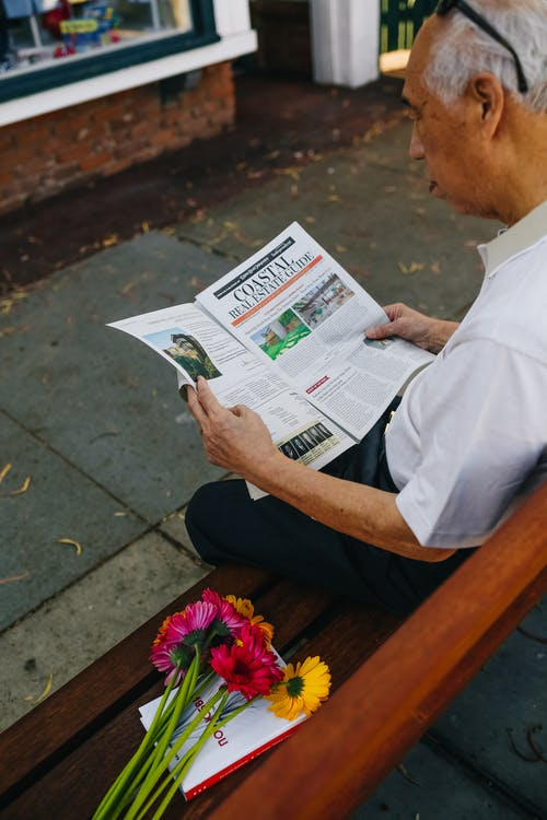 Person in White Shirt and Black Pants Sitting on Brown Wooden Bench Reading Newspaper