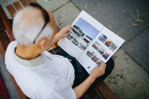 Man in White Button Up Shirt Holding Newspaper
