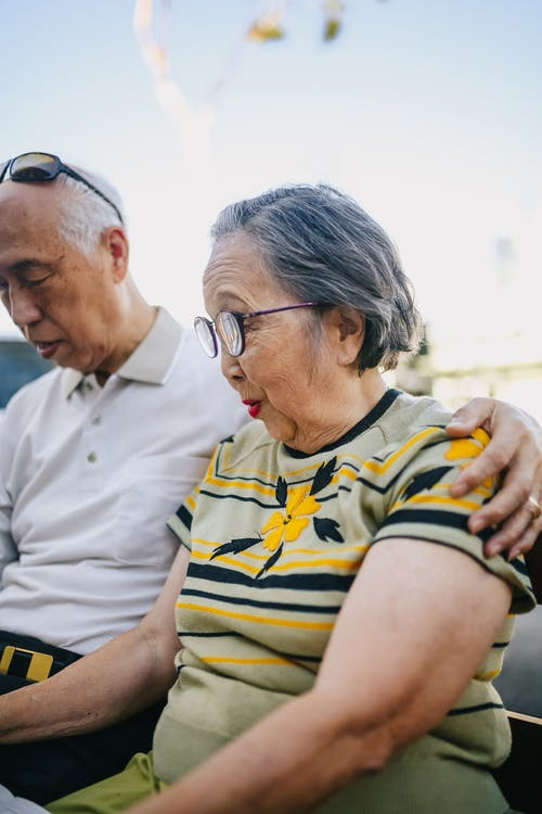 Elderly Couple Sitting on Wooden Bench