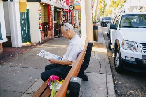 Man in White Shirt Sitting on Brown Wooden Bench Reading Newspaper