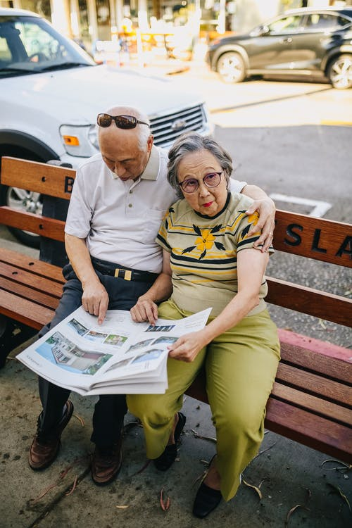 Elderly Couple Sitting on Wooden Bench