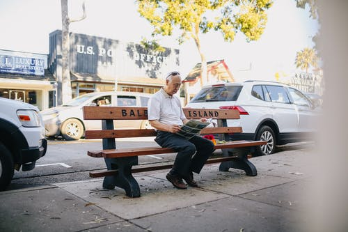 Elderly Man Sitting on the Bench Reading a Newspaper