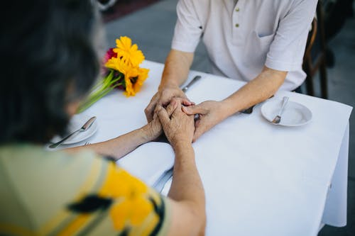 Elderly Couple Holding Hands on the Table