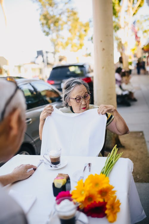 Old Lady Putting the Table Napkin on Her Lap