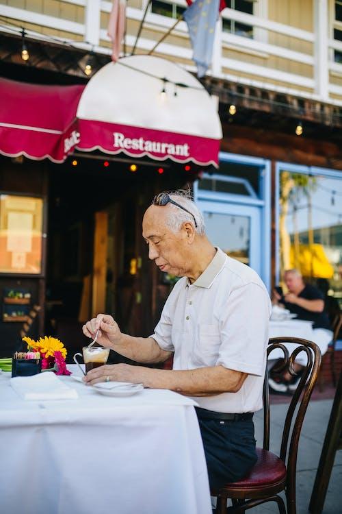 Uomo In Camicia Bianca Abbottonata Seduto Sulla Sedia Con Il Suo Caffè