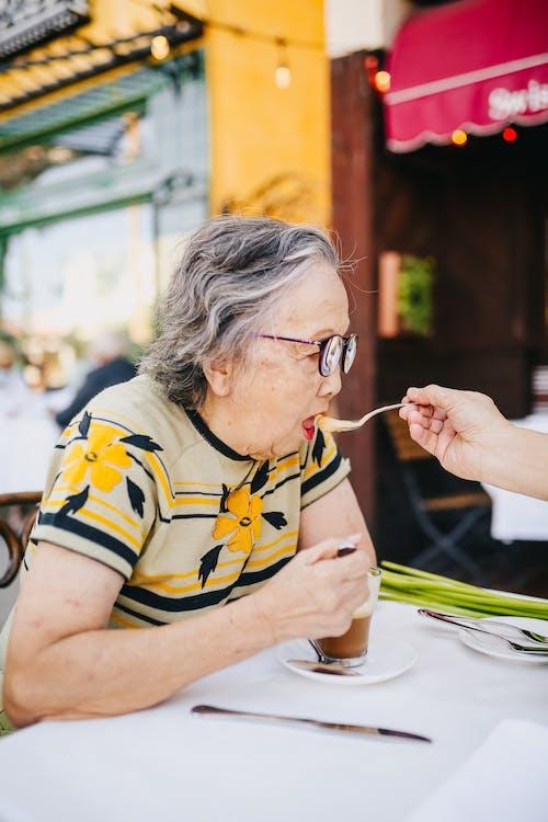 Woman in Yellow and Black Stripe Shirt Wearing Eyeglasses Eating
