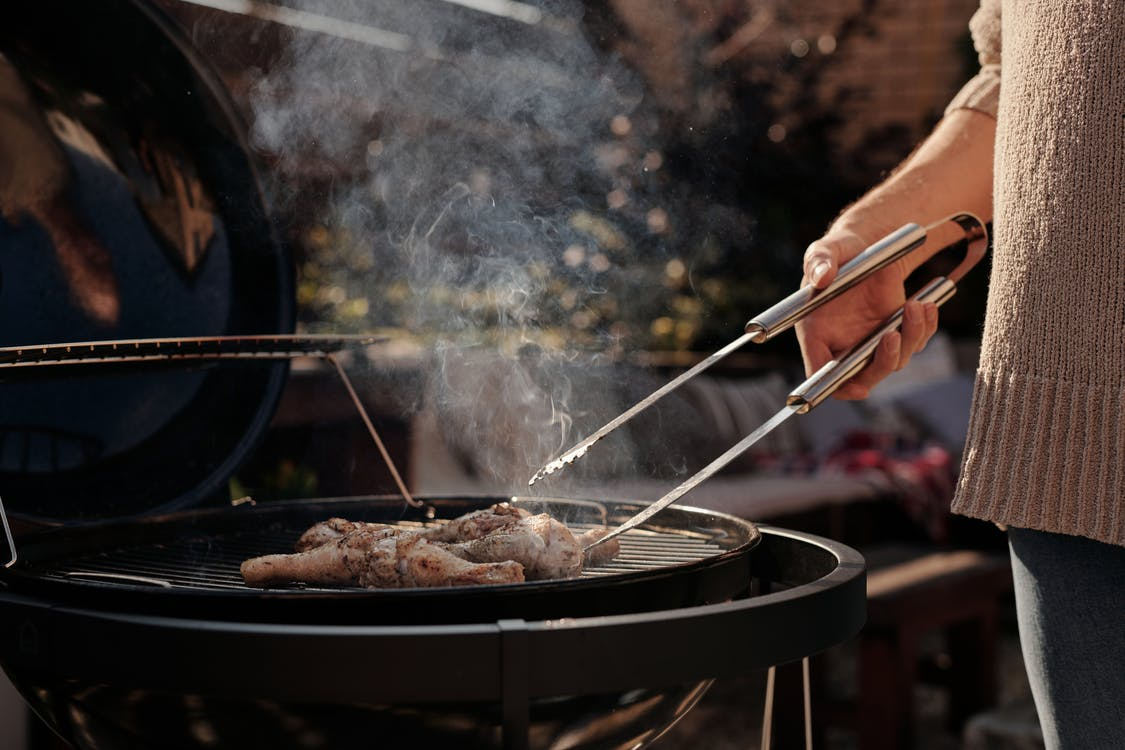 Person Holding Stainless Steel Fork and Knife Slicing Meat on Black Round Pan