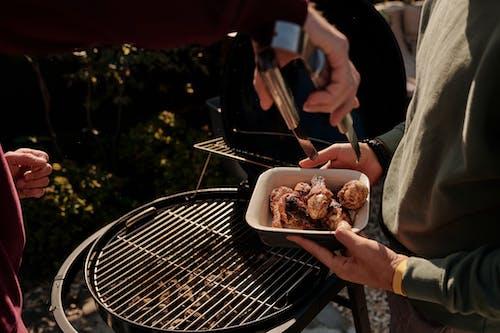 Orang Yang Memegang Garpu Dan Pisau Mengiris Daging Di Panggangan Arang Hitam