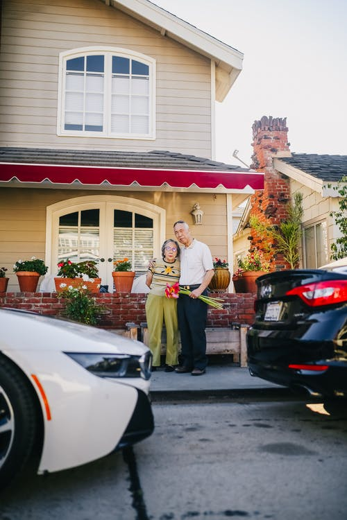 Elderly Couple Standing Outside Their House