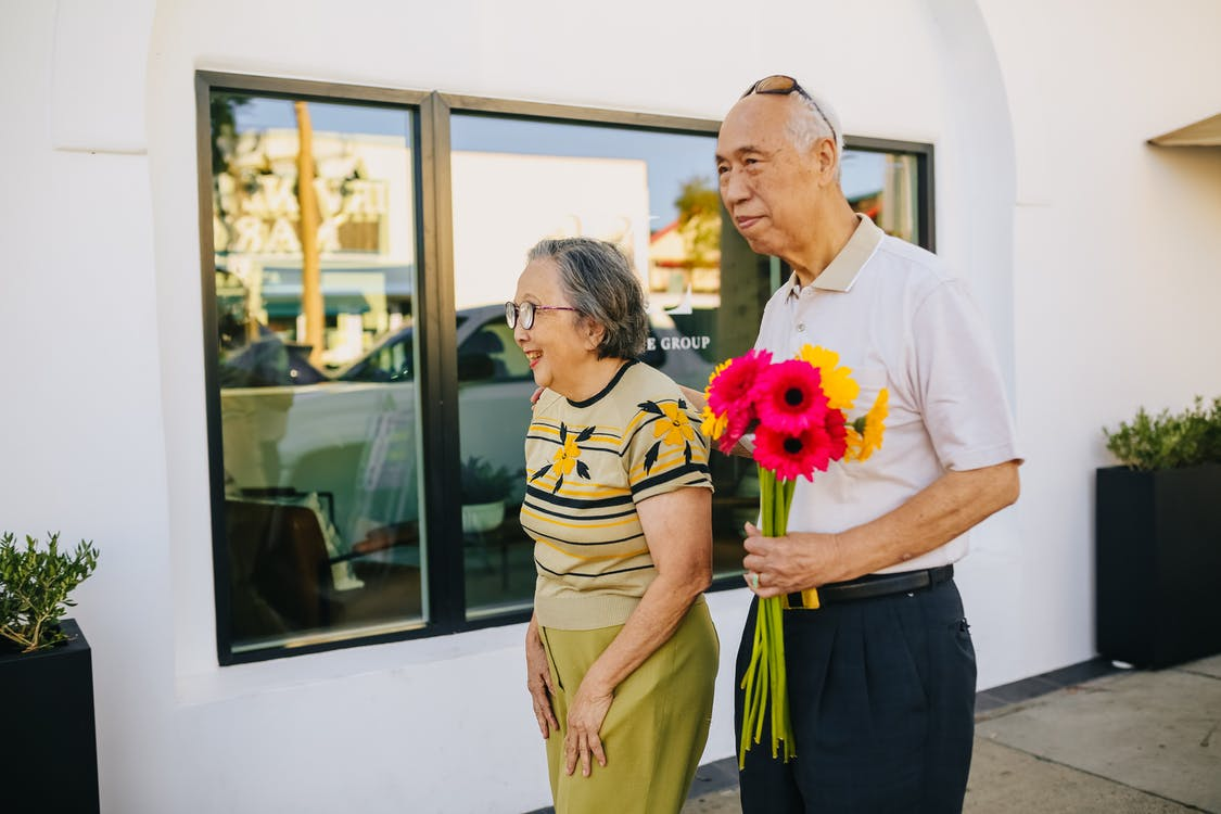 Elderly Man Holding Flowers While Walking with His Wife