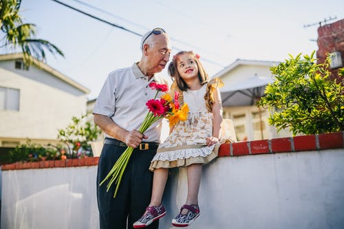 Old Man Holding Flowers with His Grandchild