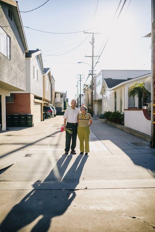 Man in Yellow Jacket and Black Pants Walking on Sidewalk