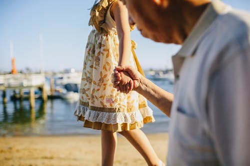 Grandfather Holding His Granddaughter's Hand while Walking