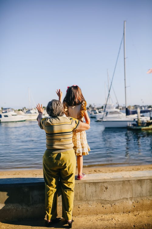 Grandma with Her Granddaughter Standing on the Shore