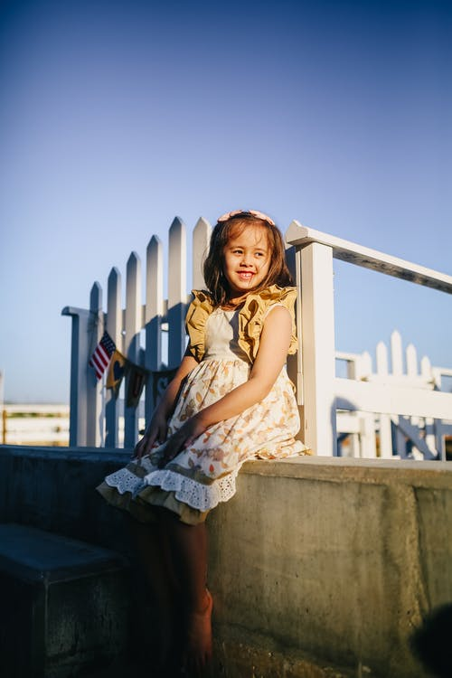 Girl in White and Brown Floral Dress Sitting on Concrete Bench