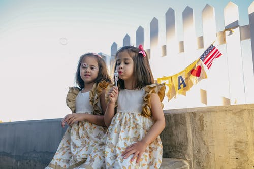 2 Girls in White and Brown Floral Dresses Blowing Bubbles