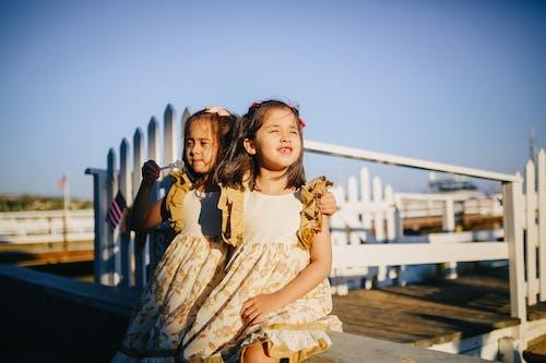 Girls in White Dress Standing on Wooden Dock