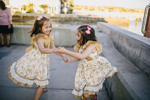 2 Girls in White Floral Dress Dancing on the Street