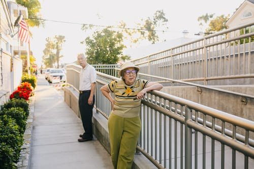 Elderly Couple Standing on the Street Leaning on the Railing