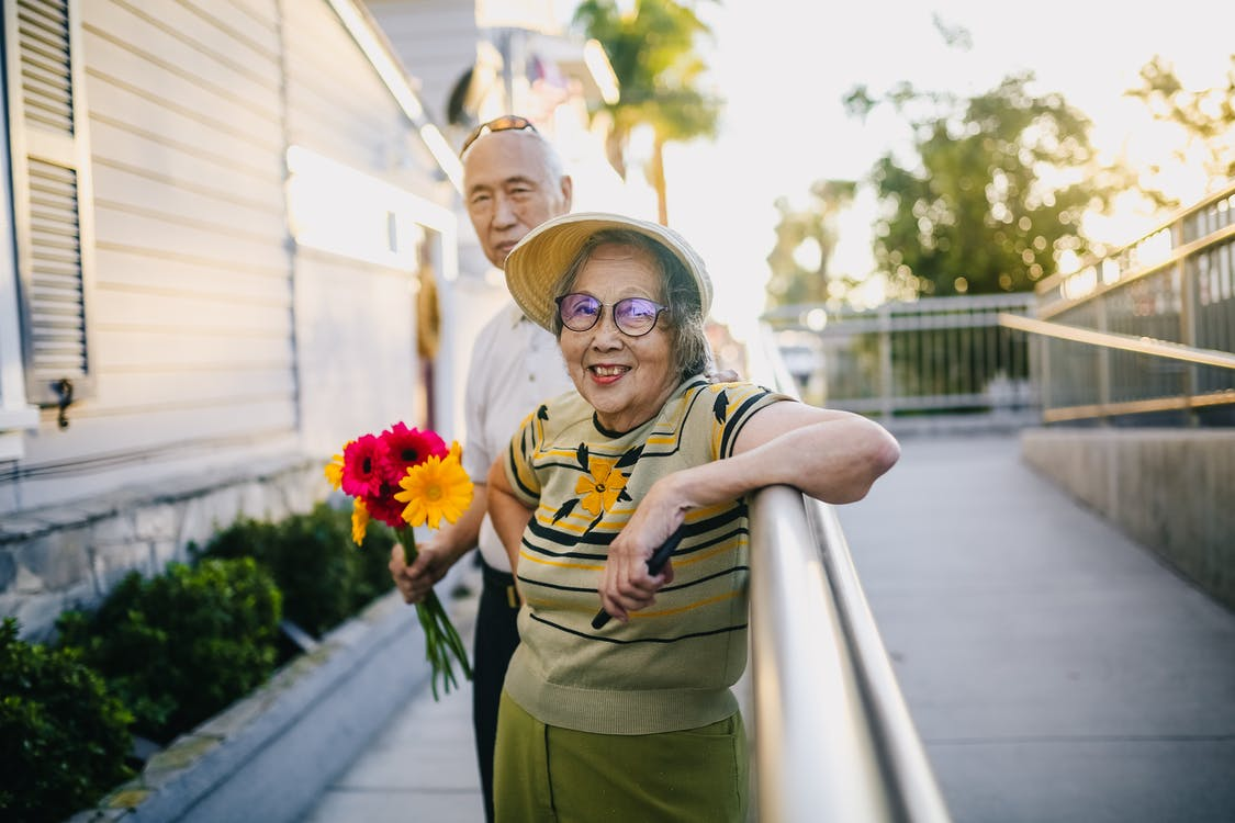 Elderly Man Holding Bouquet of Flowers With His Wife Smiling