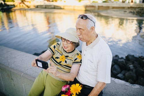 Elderly Couple Sitting on Concrete Bench