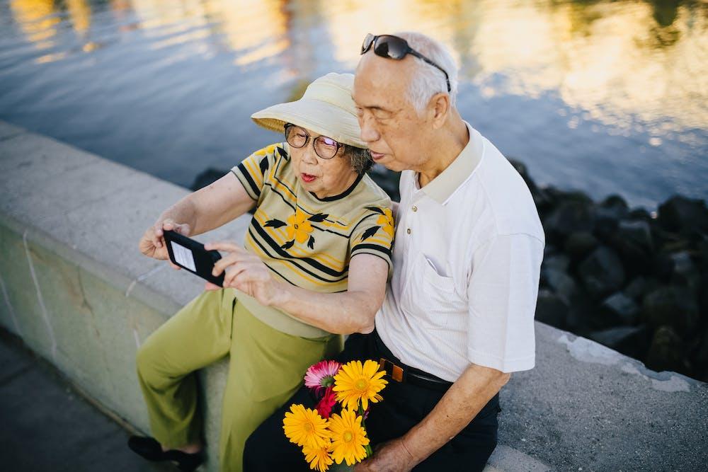Elderly couple sitting on a concrete bench.   Photo: Pexels