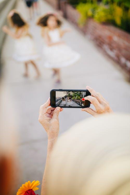 Persona Che Tiene Smartphone Nero Che Cattura Foto Di Bambini Che Ballano Per Strada
