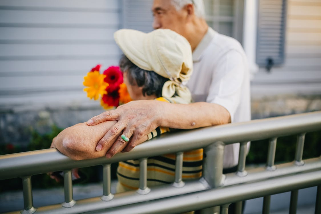 Couple Standing on the Street Holding Flowers