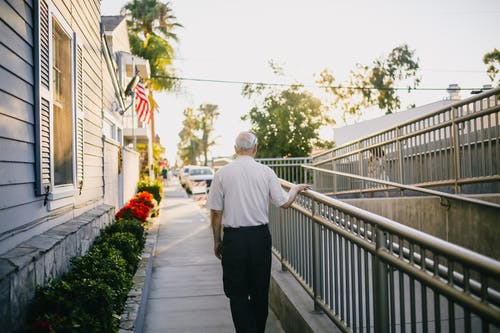 Man in White Shirt and Black Pants Standing on Gray Concrete Pathway