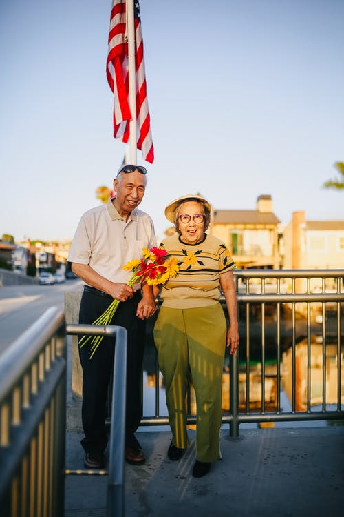 Elderly People Standing Beside A Handrail