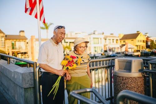 Pasangan Lansia Memegang Buket Bunga Sambil Berpegangan Tangan