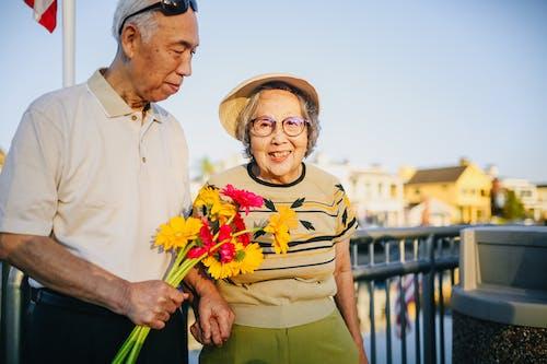 Coppia Di Anziani Che Tengono Le Mani E Che Tengono I Fiori