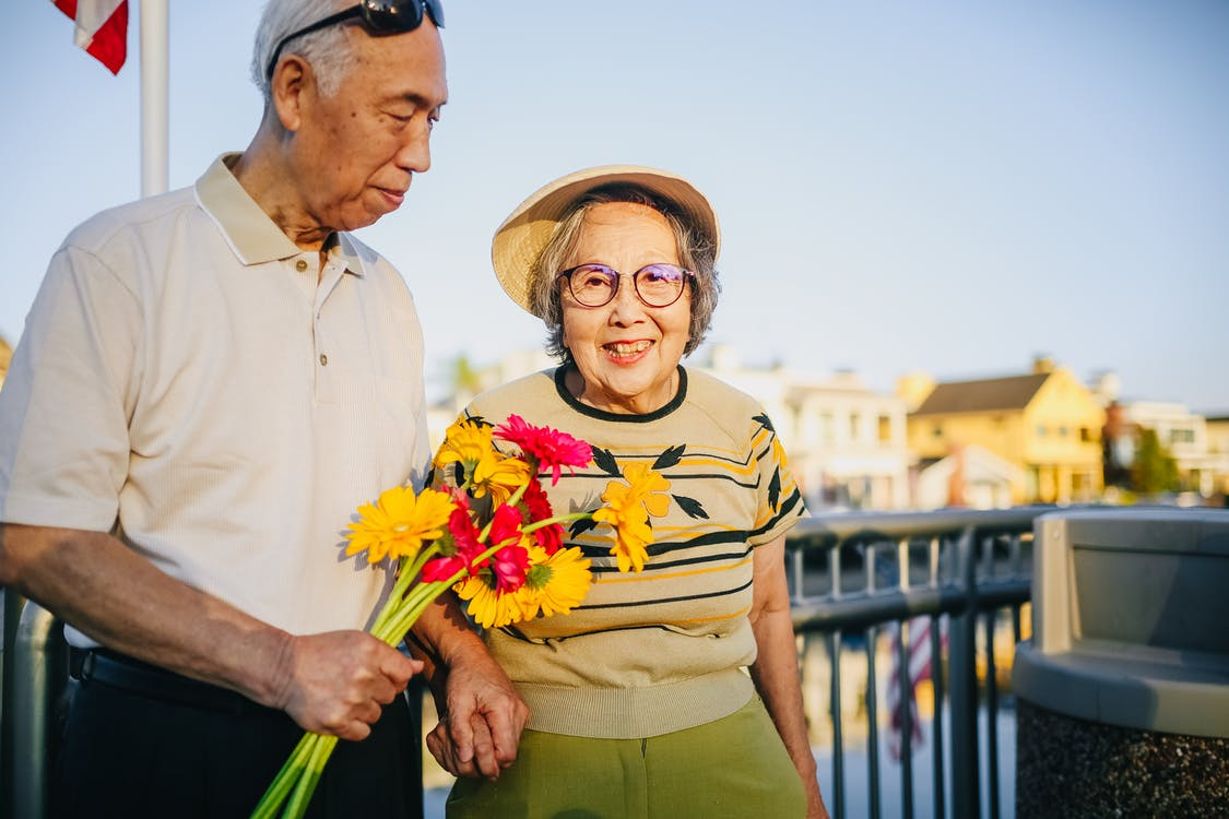 Elderly Couple Holding Hands and Holding Flowers