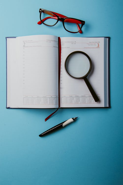 Opened notebook with magnifying glass and eyeglasses on table