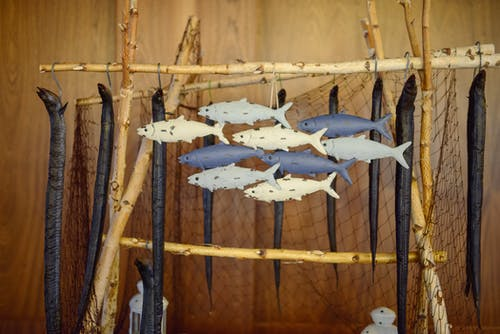 Smoked long bodied fish hanging on decorative campfire cooking stand