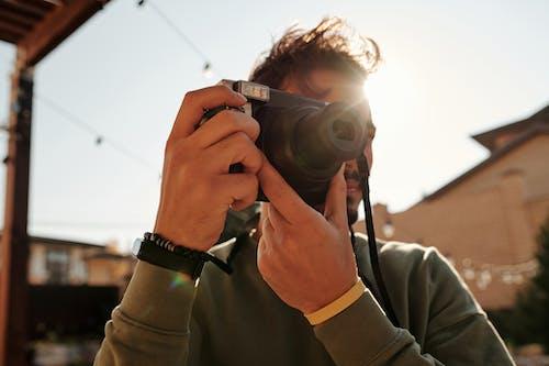 A Man Taking a Photo Using a Polaroid Camera