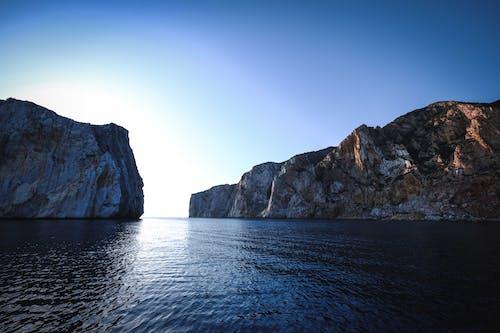Picturesque view of high vertical rocks with barren terrain in rippled ocean with horizon