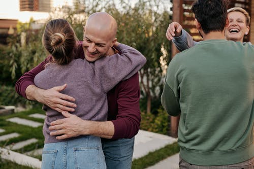 Cheerful friends hugging and smiling while spending time together in suburban yard during weekends