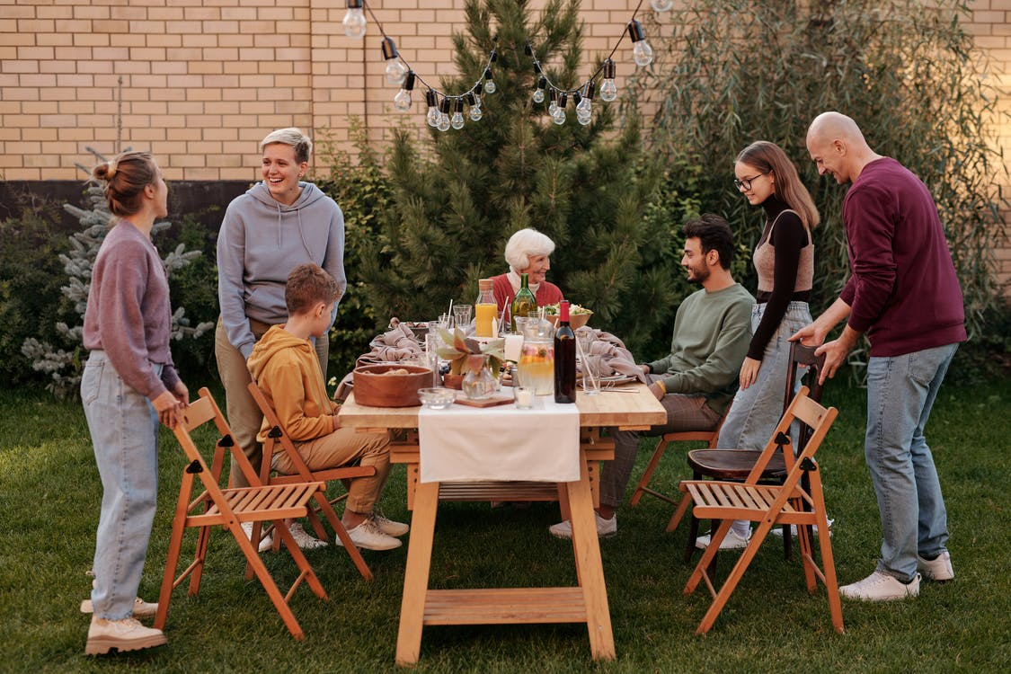 Happy family members talking and sitting down to eat tasty food at big wooden table in backyard in daytime