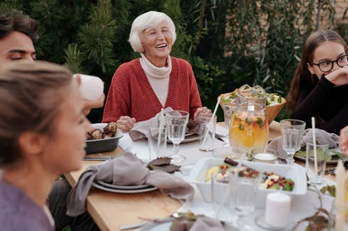 Smiling elderly woman with family and friends enjoying dinner at table backyard garden
