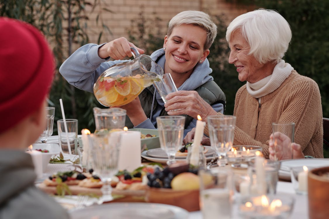 Positive lady pouring drink into glass for elderly woman while having dinner with family on terrace