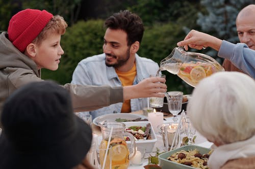Person pouring lemonade to boy during family dinner outdoors